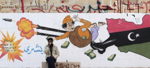 """A man sits in front of a cartoon graffiti depicting Libyan leader Muammar Gaddafi in Benghazi"" BRQ Network vía Flickr (CC BY 2.0)"