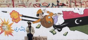 """A man sits in front of a cartoon graffiti depicting Libyan leader Muammar Gaddafi in Benghazi"" BRQ Network vía Flickr (CC BY 2.0)"